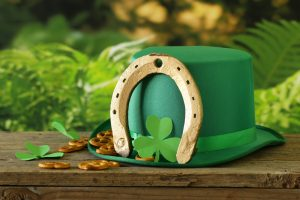 Green hat with a gold horseshoe and a shamrock on it